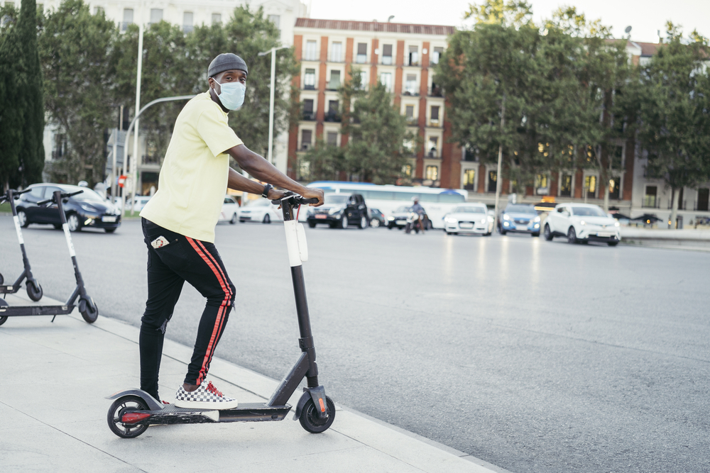 Black man with surgical mask looking to camera on electric scooter