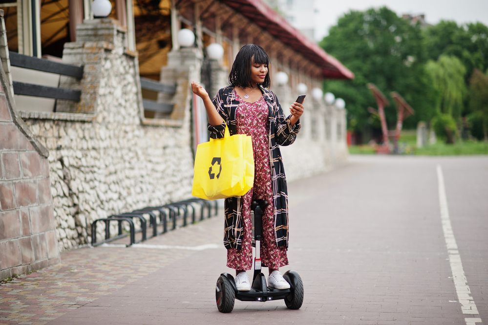 Beautiful african american woman using segway or hoverboard and